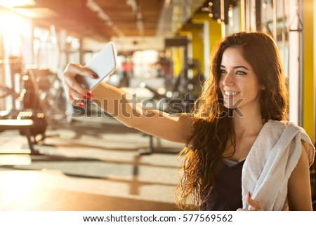 Stock Photo Young sporty woman taking a selfie with mobile phone for social networks at gym.