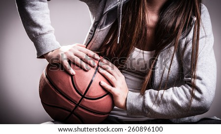 Young sporty woman teen girl long hair holding basketball on gray background