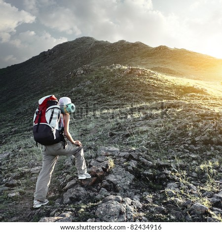 Young sporty woman with backpack walking through rocky land to the top a mountain