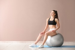 Young sporty woman with fitball near color wall