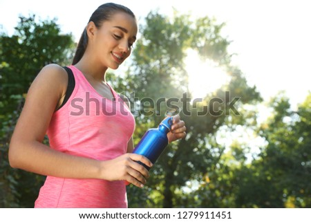 Young sporty woman with water bottle in park on sunny day. Space for text