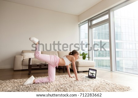 Young sporty woman working out at home, teenager doing fitness exercises on living room floor for buttocks legs shaping using online personal training program, doing yoga pilates indoors, copy space