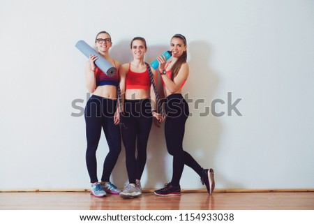 Young sporty women after training in fitness studio. Fitness, sport and healthy lifestyle concept. Group of females in sportswear standing together in front of white wall. Girls fitness exercise #1154933038
