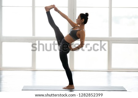 Young sporty yogi woman practicing yoga, doing Utthita Hasta Padangustasana exercise, Extended Hand to Big Toe pose, working out wearing sportswear grey pants, top, indoor full length, at yoga studio