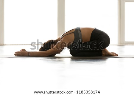 Young sporty yogi yoga woman, doing Child exercise, Balasana pose, working out, wearing sportswear, grey pants, top, indoor full length, at yoga studio. Healthy hobby wellbeing activity concept