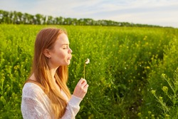 Young spring fashion redhead woman blowing dandelion in spring garden. Springtime, summertime. Trendy girl in summer landscape background. Allergic to pollen of flowers. Spring allergy