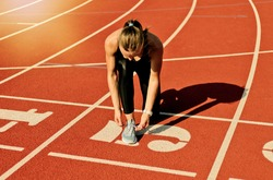 Young sprinter woman in sportswear tying shoelaces before a race on a red-coated stadium track at sunny bright day