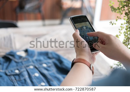 young start up small business owner holding mobile phone and take photo of her product. freelance woman use smart phone to take picture and sell cloth on website. Online selling, e-commerce concept