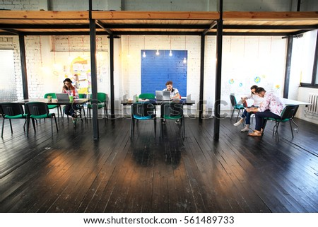 Young startup group working in modern office. Open space, laptops and paperwork. #561489733