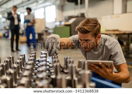 Young steel worker examining manufactured rod cylinder while using digital tablet in distribution warehouse.