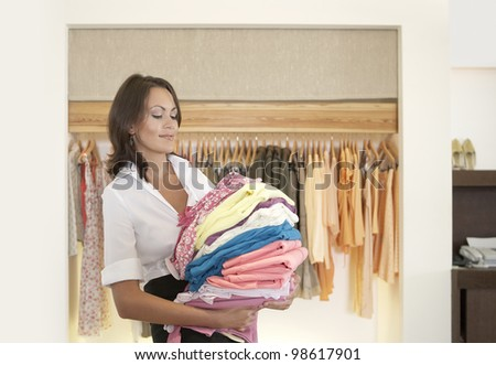 Young store attendant holding a pile of clothes in a fashion store.