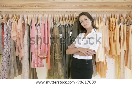 Young store attendant standing proudly by a line of clothes in a fashion store.