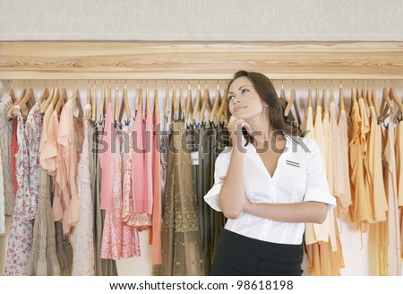 Young store attendant standing thoughtfully by a line of clothes in a fashion store.