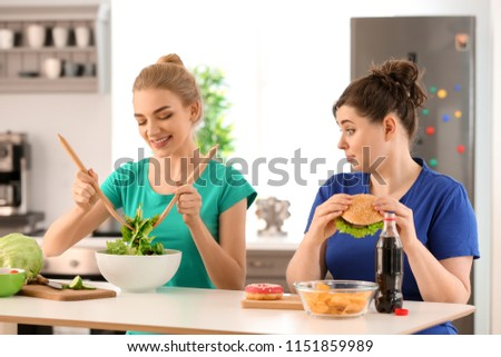 Young stout woman eating unhealthy food while her slim friend preparing salad in kitchen. Diet concept