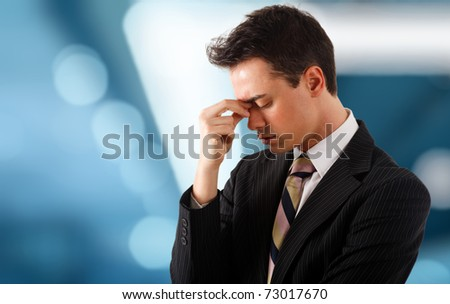 Young stressed and tired businessman. Blue blurred background.