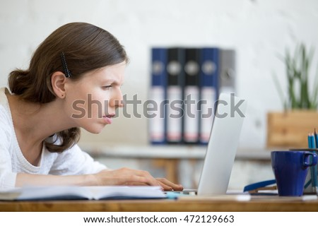 Young stressed businesswoman sitting with laptop and looking at screen with concerned facial expression. Surprised and focused business person staring at laptop computer screen worried and interested
