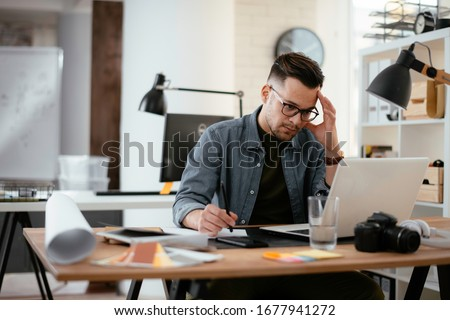 Young stressed handsome businessman working in office. Angry businessman with too much work in office.
