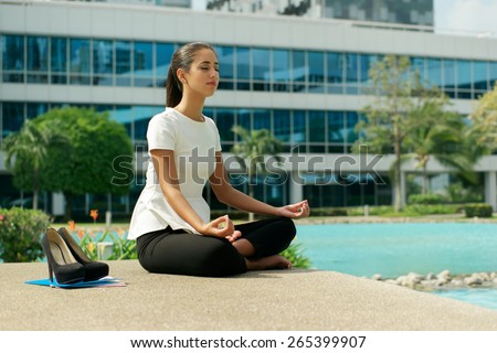 Young stressed hispanic business woman doing yoga outside office building, sitting in lotus position with hands on knees in the street. Concept of long working hours and need of stress free break