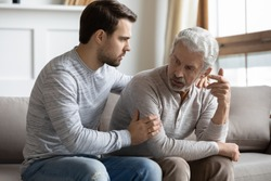 Young stressed man comforting irritated mature old father, sitting together on couch. Worried grownup son feeling sorry, asking forgiveness to angry offended unhappy middle aged hoary daddy.
