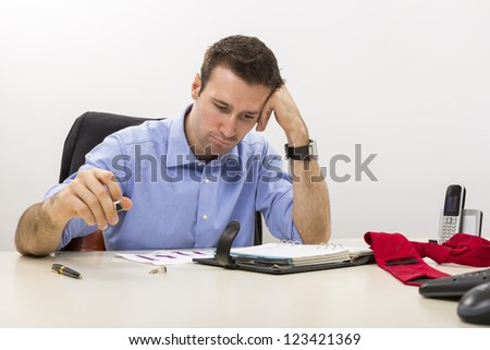 Young stressed manager analyzing some charts with hand at his temple.