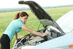 Young stressed woman having trouble with her car breakdown on the road and she waiting someone can help her. Conceptual of car accident on the road
