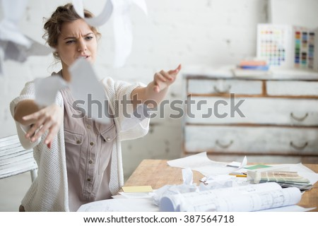 Young stressed woman sitting at desk in a little office or home mad at work, ripping documents with frustrated facial expression. Throwing around scraps of paper. Negative human emotions