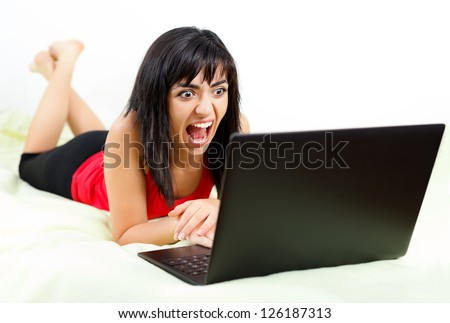Young stressed woman yelling in the front of her laptop.