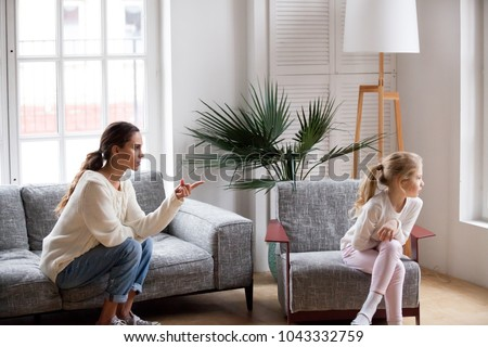 Young strict mother or sister scolding stubborn sulky kid girl in living room at home, offended daughter ignoring angry mom reprimanding disobedient child for bad behavior, family conflict concept ストックフォト ©