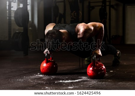 Young strong fit sweaty muscular veteran  man with scars on big muscles doing push ups on two big old heavy kettlebells with his hands for hard core cross workout training on the gym floor and rehab