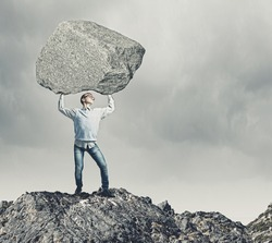 Young strong man holding huge stone above head