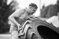 Young strong man lift up big heavy wheel on strenth competition