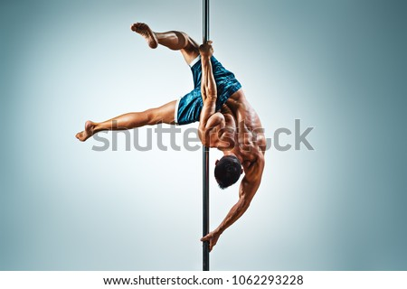 Young strong man pole dancing on blue and white background Сток-фото ©