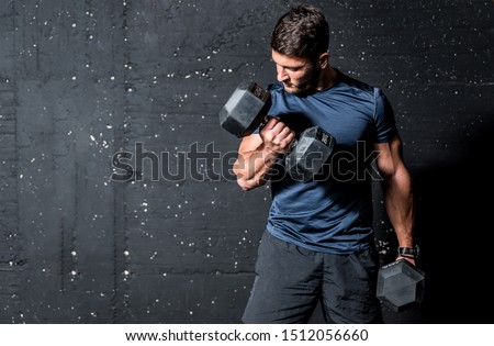 Young strong muscular sweaty man biceps muscle workout training with heavy dumbbell weight in the gym dark image with shadows real people