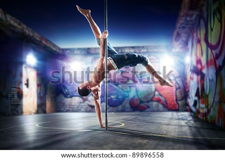 Young strong pole dance man on urban background.