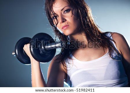 Young strong sexy woman with dumbbell. Camera angle view.