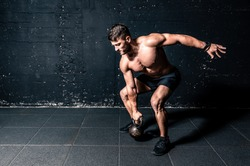 Young strong sweaty focused fit muscular man with big muscles holding heavy kettlebell for cross swing training hard core workout in the gym real people