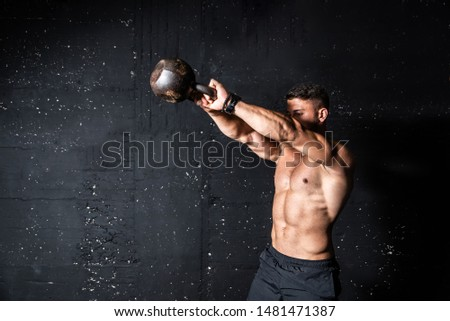 Young strong sweaty focused fit muscular man with big muscles holding heavy kettlebell for swing cross training hard core workout in the gym