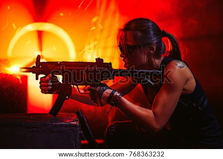 Stock Photo Young strong woman warrior shooting from machine gun in dramatic urban night scene. Tattoo on body.