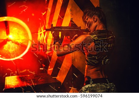 Stock Photo Young strong woman warrior with big gun in dramatic urban night scene. Tattoo on body.