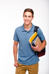 Young student boy smiling, looking at camera and holding books. Isolated on white background