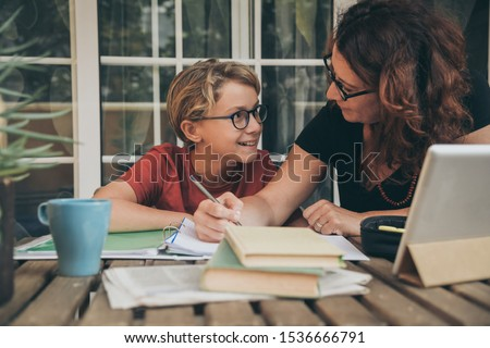 Young student doing homework at home with school books, newspaper and digital pad helped by his mother. Mum writing on the copybook teaching his son. Education, family lifestyle, homeschooling concept