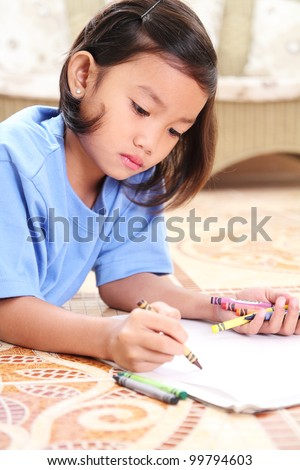 young student drawing with crayons.