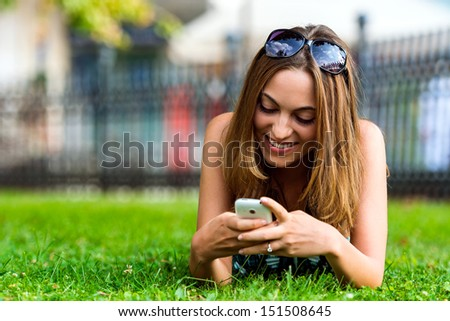 Young Student Girl (21) Browsing The Internet With Her Cell Phone in City Park