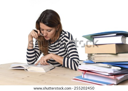 young student girl concentrated studying with textbook at college library desk with piles of books preparing MBA test or exam in academic wisdom and education concept