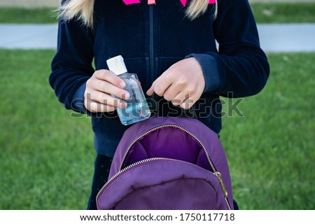 Young student girl holding hand sanitizer bottle putting to her school purple backpack. Ready for new school year with pandemic restrictions. School reopening. Return back to school, new life concept.