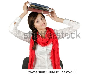 Young student girl with her books in hand at head, smiling and looking at the camera