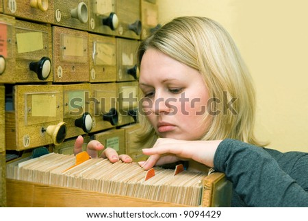 Young student girl working with library card index