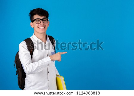Young student holding yellow book carrying backpack points with on finger smiles on a blue background.