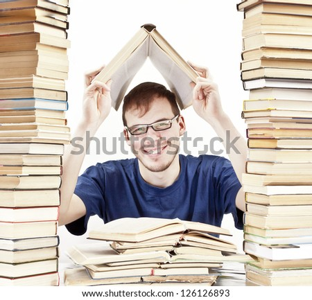 young Student learning at home between tall stacks of books in the form of skyscrapers