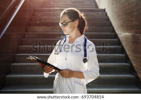 Young student medical student looks at the paces standing on the steps